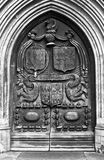 Medieval door. Old medieval wooden door carved with a traditional coat of arms royalty free stock photography