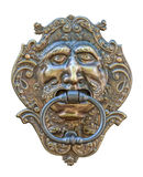 Medieval door knocker, bronze human head cutout. Old medieval bronze door knocker in shape of human head isolated on white background with clipping path. For stock photo