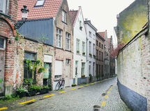 Medieval empty side street of Bruges, Belgium, with a bike parke Royalty Free Stock Images