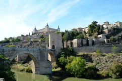 Medieval entrance to the historical city of Toledo (Spain). Medieval bridge in the historical city of Toledo (Spain), with historical buildings as a background Royalty Free Stock Photography