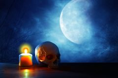 Medieval and fantasy halloween concept. Human skull, full moon and burning candle over old wooden table at scary night. Medieval and fantasy halloween concept royalty free stock photos