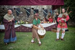 Medieval musicians performing ancient tunes with instruments like bagpipe, bass drum and flute. During a medieval festival re-enactment three musicians play royalty free stock photography