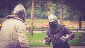 Medieval fight. Two men practice medieval fighting in a park Stock Images