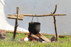 Medieval fire and pot. Medieval outdoor fire and metal pot Stock Photography