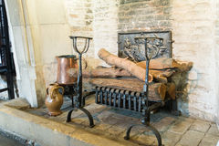 Medieval fireplace. Details of the ancient fireplace full of wooden logs. Medieval livingroom interior Royalty Free Stock Photography