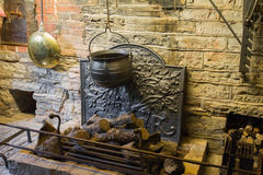 Medieval fireplace. Details of an ancient fireplace with old metal pot hanging over coals. Medieval house interior Royalty Free Stock Photos