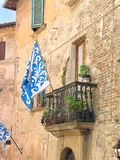 Medieval flag in Tuscan town. Blue flag symbolizing one of the contradas of Montepulciano in Tuscany, Italy Royalty Free Stock Photography
