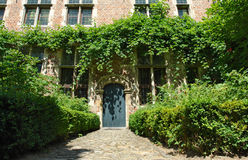 Medieval Flemish house facade. Facade of medieval Flemish house in the Louvain (Belgium) beguinage. Road with cobblestones Royalty Free Stock Images