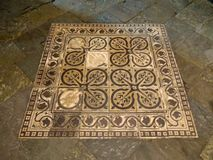 Medieval floor tiles at le Mont st Michel france. These tiles are set into the floor of the crypt at the Abbey of Mont st Michel, Brittany, France. The ceramics Stock Photo