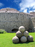 Medieval fortress. Stack of stone cannonballs in front of a bastion of the medieval castle Royalty Free Stock Photos