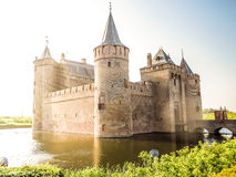 Medieval fortress with moat lit by sunshine. Medieval fortress surrounded by water brightly lit by sunshine Royalty Free Stock Photos