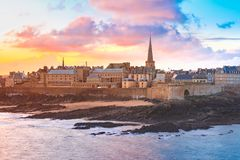 Medieval fortress Saint-Malo, Brittany, France. Beautiful view of walled city Saint-Malo with St Vincent Cathedral at sunrise at high tide. Saint-Maol is famous stock photo