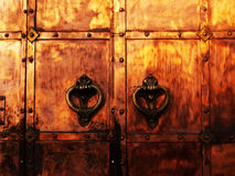 Medieval gate#1. Medieval coppery gates with wrought knockers Stock Photography