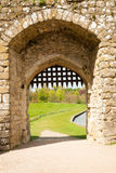 Medieval gate. Detail of medieval stone castle gate, with grass and mote in the background Royalty Free Stock Photography