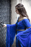 Medieval girl opening door Stock Images