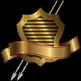 Medieval gold shield with two spears and ribbon. Medieval gold shield with two spears and gold ribbon on a black background Stock Photo