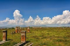 Medieval graveyard in greenery under blue skies with fluffy whit. E clouds Stock Photos