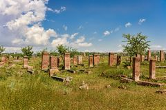Medieval graveyard in greenery under blue skies with fluffy whit. E clouds Stock Photo