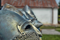 Medieval  helmets. A row of medieval silver metal helmets , laying with banners, chain-male and shields Stock Photography