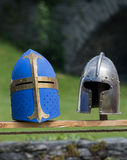 Medieval helmets. Two medieval helmets; a blue one and a silver one Stock Image