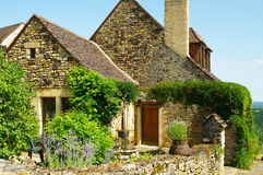 Medieval house. Medieval stone house and garden some plants in ancient village in dordogne in france against blue sky Royalty Free Stock Image