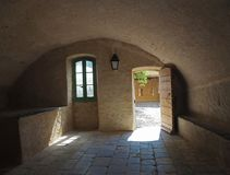 Medieval house with barrel vault open door lantern green window. And yard view yellow stone walls and cobblestone paving in corte castle Stock Images