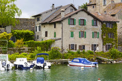 Medieval houses by the lake in Yvoire. YVOIRE, FRANCE - MAY 24, 2013: The view towards medieval city by the Lake Geneva. A few motorboats are moored at the Stock Photography