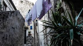 Medieval houses in the narrow streets of Dubrovnik with hanging clothes and stone stairs stock photos