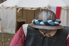 Medieval Iron Helmet and Clothes and white Tent in background Stock Image
