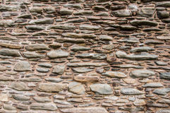 Medieval irregular stone wall background. Medieval stone wall particular with stones of different sizes and shapes Royalty Free Stock Photos