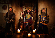 Medieval king with his knights in ancient castle interior.  royalty free stock images