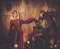 Medieval king with his queen in castle interior. Stock Image