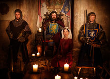Medieval king with his queen and knights on guard in ancient castle interior.  stock image