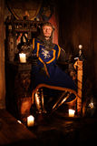 Medieval king on throne in ancient castle interior. Royalty Free Stock Photography
