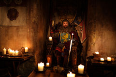 Medieval king on throne in ancient castle interior. Royalty Free Stock Photos