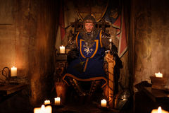 Medieval king on throne in ancient castle interior. Royalty Free Stock Images