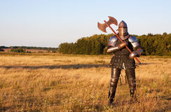 Medieval knight. In the field with an axe stock photography