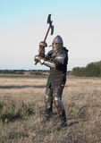 Medieval knight. In the field with an axe royalty free stock photo