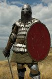 Medieval knight. A picture of a man dressed as a medieval knight with armor, buckler and sword in hand. He is standing in an open field Stock Image