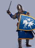 Medieval knight is attacking. Medieval knight on grey background Stock Photo