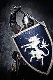Medieval knight in full armour. Medieval knight against stone wall Royalty Free Stock Image