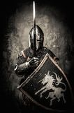 Medieval knight in full armour. Medieval knight against stone wall Royalty Free Stock Photo