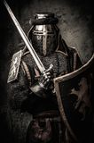 Medieval knight in full armour. Medieval knight with a sword against stone wall Stock Image