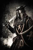 Medieval knight in full armour. Medieval knight with a sword against stone wall Stock Images