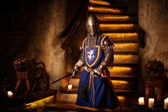 Medieval knight on guard in ancient castle  interior. Stock Photos