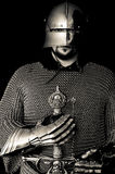 Medieval Knight with Helmet and Sword. Medieval costume including helmet, chain mail, sword and gauntlets stock images