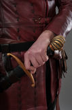 Medieval knight holding hand on his sword. Closeup Stock Photo