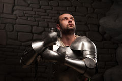 Medieval knight kneeling with sword. Closeup portrait of inspired medieval knight looking up and kneeling with sword on a dark stonewall background Stock Photo