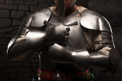 Medieval knight kneeling with sword. Closeup portrait of medieval knight keeping sword on chest on a dark stonewall background Royalty Free Stock Photo