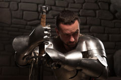 Medieval knight kneeling with sword Stock Photos